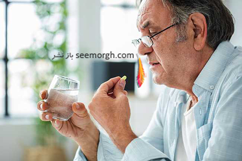 مرد در حال خوردن دارو