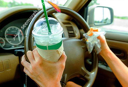 causes_of_bloating_hands_holding_steering_drink_and_food.jpg