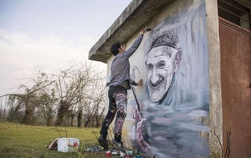 سینا رمضانی مقدم در حال طراحی چهره روستاییان بر دیوار