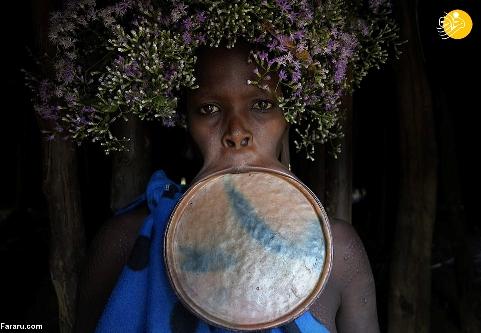 زنی از قبیله با بشقابی در دهان