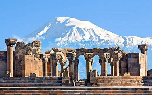 بقایای سازه تاریخی کلیسا با پس زمینه ای از کوه مملو از برف