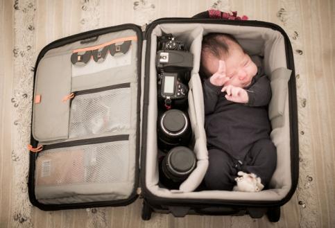 نوزاد کوچک در کیف وسایل عکاسی